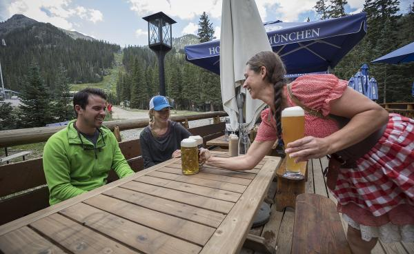 Waitress in dirndl serves beer on a deck with mountain views